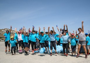 Mykonian school children jump for joy after helping to clean up Korfos Beach.